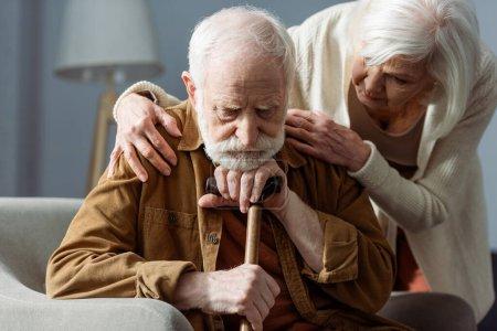 Photo pour Homme âgé, malade de démence, assis avec un bâton de marche, tandis que sa femme le regarde et lui touche les épaules - image libre de droit