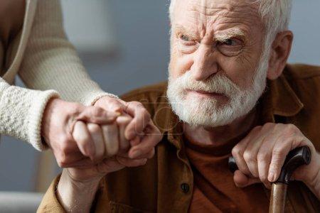 Photo pour Vue partielle de la femme tenant la main du mari aîné, malade de démence - image libre de droit