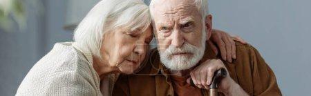 Photo pour Image horizontale de la femme âgée avec les yeux fermés embrassant mari, malade sur la démence - image libre de droit