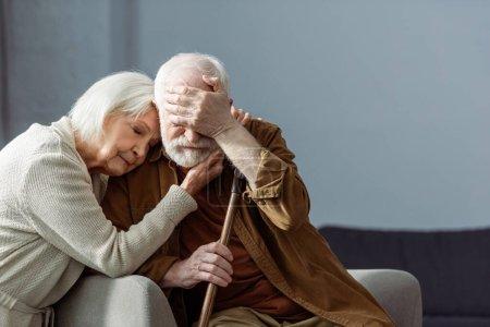 Photo pour Homme âgé, malade de démence, couvrant les yeux avec la main tandis que la femme l'embrassant avec les yeux fermés - image libre de droit