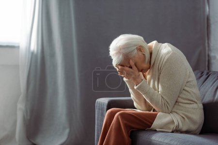 Photo for Depressed senior woman sitting on sofa with bowed had and obscuring face with hands - Royalty Free Image