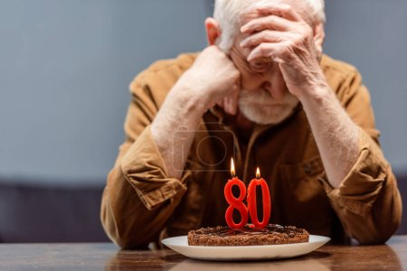 Photo for Depressed, lonely senior sitting near birthday cake with number eighty - Royalty Free Image