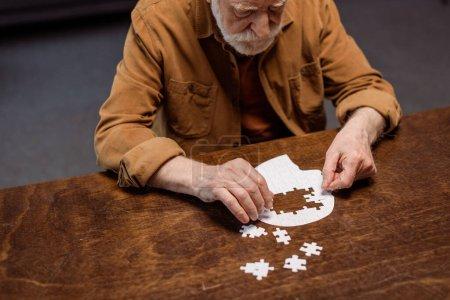 Photo pour Vue grand angle de l'homme âgé jouant puzzle comme thérapie de démence - image libre de droit