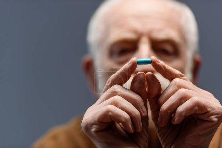 Photo pour Foyer sélectif de l'homme âgé regardant la pilule dans ses mains - image libre de droit