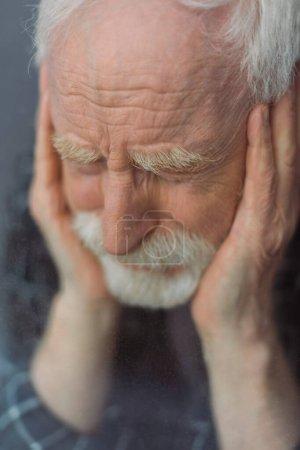 Photo pour Foyer sélectif de l'homme âgé, déprimé avec les yeux fermés touchant le visage près du verre de fenêtre - image libre de droit