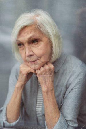 Photo pour Triste femme âgée regardant loin à travers le verre de fenêtre - image libre de droit