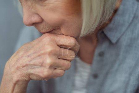 Photo pour Vue recadrée d'une femme solitaire âgée tenant la main près du menton - image libre de droit