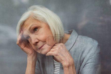 Photo pour Solitaire femme âgée regarder loin tout en se tenant par la fenêtre - image libre de droit