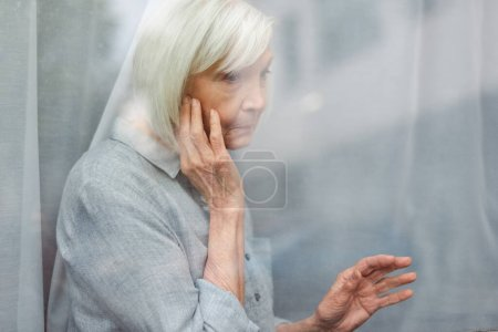 Photo for Depressed senior woman touching face and window glass while looking away - Royalty Free Image