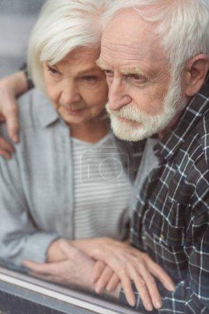 Photo pour Homme âgé réfléchi et sa femme, malade de démence, se tenant la main par la fenêtre - image libre de droit