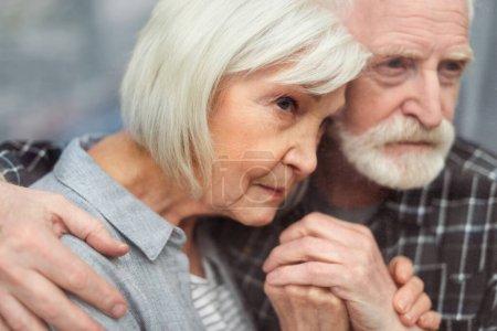 Photo pour Homme âgé réfléchi tenant la main de sa femme, malade de démence, tout en regardant par la fenêtre - image libre de droit