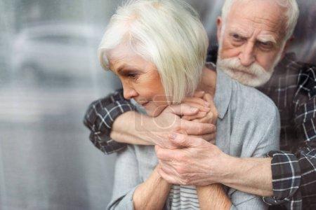 Photo pour Bouleversé senior homme étreignant femme, malade sur la démence, tout en se tenant par la fenêtre - image libre de droit