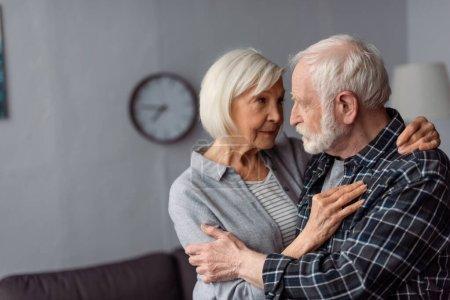 Photo pour Femme âgée étreignant son mari, malade de démence, debout face à face - image libre de droit