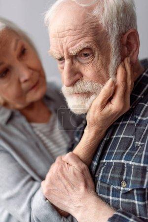 Photo pour Femme âgée touchant le visage du mari souffrant de démence - image libre de droit