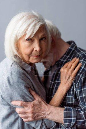 Photo pour Bouleversé femme âgée regardant la caméra tout en embrassant mari souffrant de démence - image libre de droit
