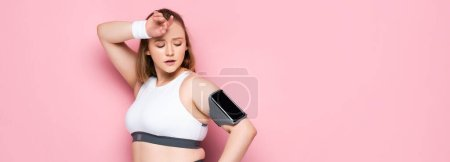 horizontal image of tired overweight girl looking at smartphone in armband while touching forehead on pink