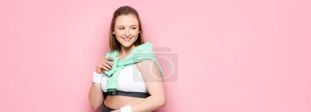 Photo for Panoramic crop of beautiful overweight girl with sweatshirt over shoulders smiling while looking away on pink - Royalty Free Image