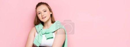 Photo pour Site web tête de fille en surpoids avec sweat-shirt sur les épaules souriant à la caméra sur rose - image libre de droit