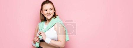 Photo pour Image horizontale d'une jolie fille en surpoids avec sweat-shirt sur les épaules souriant tout en regardant loin sur rose - image libre de droit