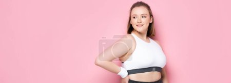 Photo for Website header of attractive overweight girl standing with hand on hip on pink - Royalty Free Image