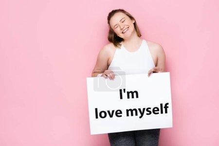 Photo pour Joyeuse fille en surpoids avec les yeux fermés tenant la pancarte avec je m'aime inscription sur rose - image libre de droit