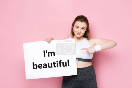 Photo for Smiling overweight girl pointing with finger at placard with I am beautiful inscription on pink - Royalty Free Image