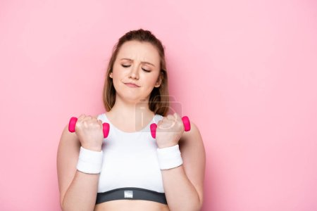 Photo pour Diligent plus la formation des filles de taille avec haltères avec les yeux fermés sur rose - image libre de droit