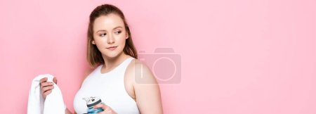 pretty plus size girl holding sports bottle and white towel while looking away on pink