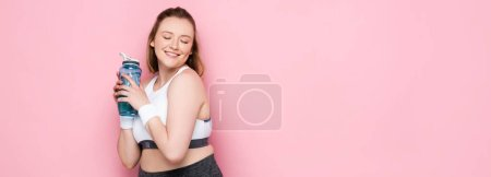 horizontal image of pretty overweight girl holding sports bottle and smiling with closed eyes on pink