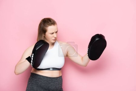 Photo for Serious size plus girl training in boxing pads on pink - Royalty Free Image