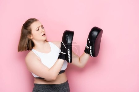 Photo for Scared size plus girl training in boxing pards on pink - Royalty Free Image