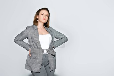 confident, elegant overweight girl looking at camera while posing with hands on hips on grey