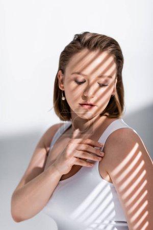 Photo pour Belle fille en surpoids touchant haut blanc sur blanc dans la lumière du soleil avec des ombres - image libre de droit