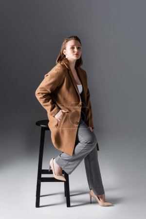 full length view of serious, attractive overweight girl posing on high stool with hand in pocket on grey