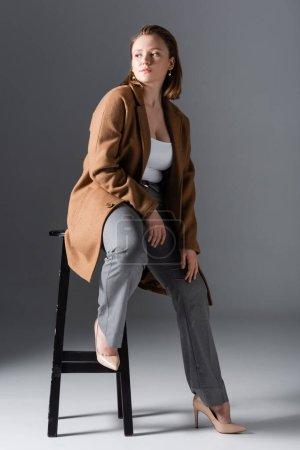 Photo pour Pleine longueur vue de confiant, élégant fille en surpoids posant sur chaise haute et regardant loin sur gris - image libre de droit