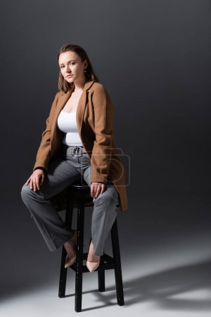 full length view of attractive, stylish overweight girl sitting on high stool and looking at camera while posing on grey
