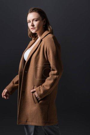 Photo pour Belle, confiante fille en surpoids en manteau regardant la caméra tout en tenant la main dans la poche isolé sur gris - image libre de droit