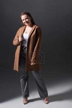 Photo pour Vue pleine longueur de sourire, belle fille plus la taille dans des vêtements à la mode en regardant la caméra sur gris - image libre de droit