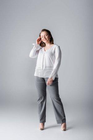 Photo pour Vue pleine longueur de fille en surpoids élégant toucher les cheveux tout en posant avec les yeux fermés sur le gris - image libre de droit