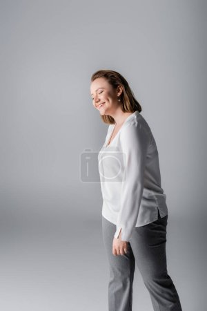 Photo for Smiling, elegant overweight girl in white blouse posing with closed eyes on grey - Royalty Free Image