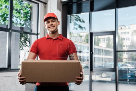 Photo for Positive delivery man in cap holding carton box and looking at camera - Royalty Free Image