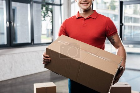 Photo for Cropped view of positive delivery man holding carton box - Royalty Free Image