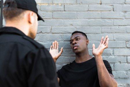 Photo pour Foyer sélectif de l'homme afro-américain avec les mains levées en regardant policier, concept de racisme - image libre de droit