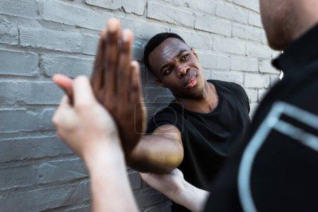 Photo pour Foyer sélectif de l'homme afro-américain blessé regardant policier toucher la main, concept de racisme - image libre de droit