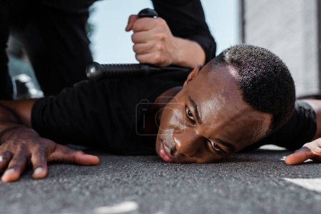 Photo for Selective focus of detained african american man lying on ground near police officer with baton, racism concept - Royalty Free Image