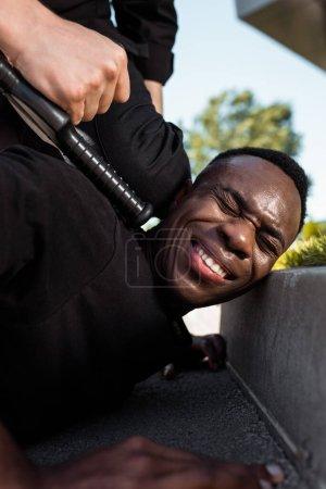 Photo pour Foyer sélectif de l'homme afro-américain détenu souffrant de douleur alors qu'il était couché sur le sol près d'un policier avec matraque, concept de racisme - image libre de droit