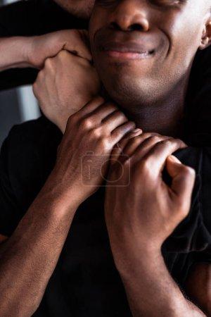 Photo pour Vue recadrée du policier étouffant l'homme afro-américain - image libre de droit