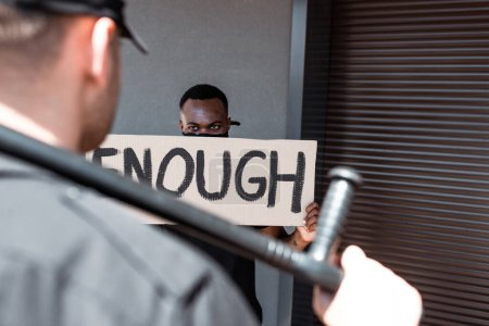 Photo for Selective focus of african american man holding placard with enough lettering near police officer with truncheon, racism concept - Royalty Free Image
