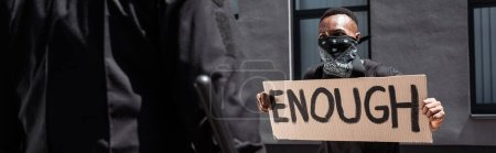 Photo for Selective focus of african american man with scarf on face holding placard with enough lettering near policeman with baton on street, racism concept - Royalty Free Image