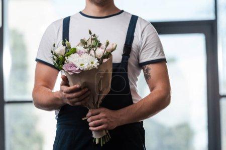 vista recortada del repartidor hombre sosteniendo ramo de flores en flor